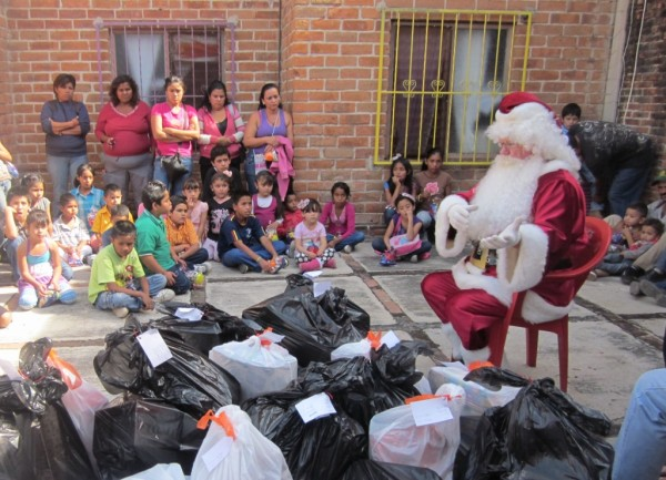Santa gets the kids' attention -- but a few are focused on the bags of presents.